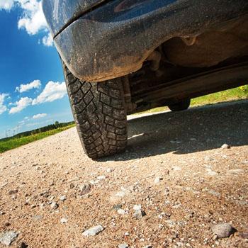 Car on gravel, tires rolling on gravel