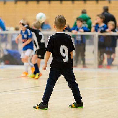 Indoor stadium, children playing football, shoes squeaks
